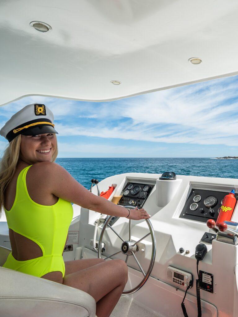 girl captains hat boat steering smiling