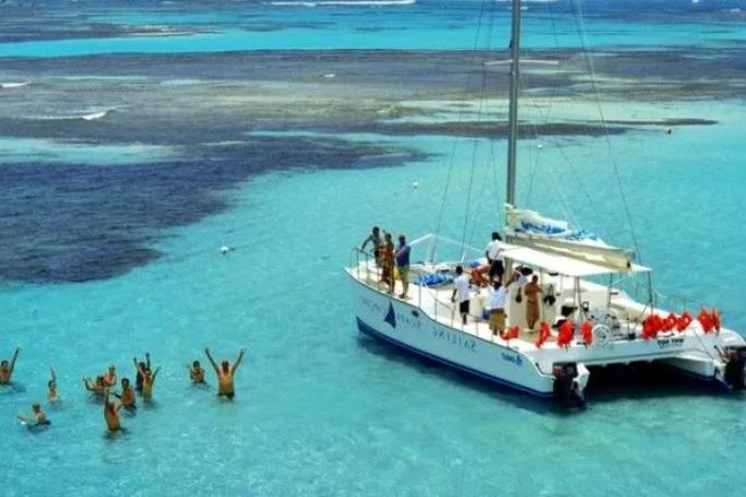 people swimming near boat in ocean